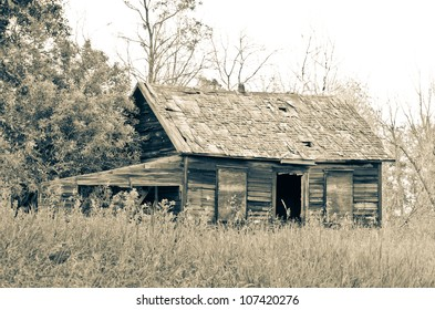A sepia toned image of an abandoned homestead
