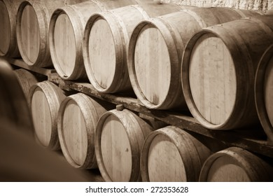 Sepia toned photo  of  winery cellar with  wooden barrels