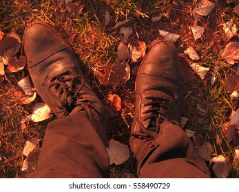 Sepia top view of a pair of worn black boots, grass and dry leaves at background. Autumn/ winter concept