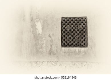 Sepia view of a carved wooden lattice covering a window in the adobe, plaster and stone wall of a traditional house in the Arabian Gulf.