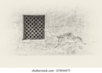 Sepia view of a carved wooden lattice covering a window in the crumbling adobe and plaster wall of an old restored building in the Arabian Gulf.