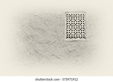 Sepia view of a gypsum plaster ventilation lattice in the adobe wall of a traditional Arabian house.