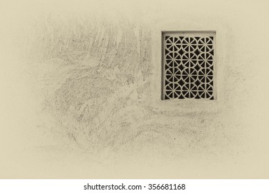 Sepia view of a lattice in an external wall which provides air and yet maintains privacy at the restored Shaikh Isa bin Ali House in Muharraq, the old capital of Bahrain.