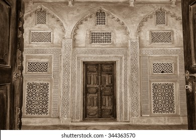 Sepia view of latticed windows and entrance seen through a doorway to the ladies' quarters of the restored traditional Arabian house of pearl trader Shaikh Isa bin Ali, Muharraq, Bahrain.