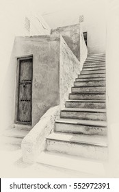 A sepia view of a stairway leading to the upper story of a traditional Arabian house with an old wooden storeroom door.
