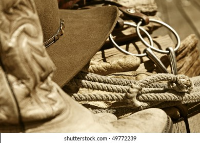 Sepia-toned rustic western image of cowboy boots, cowboy hat, rope, horse bit and stacked wood (mid-focus point).
