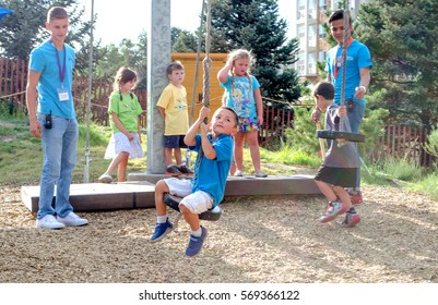 Sept 1,, 2015, denver CO USA; Children ride on a zip-line at the Denver Children`s museum, while workers help keep them safe, and get on and off the ride
