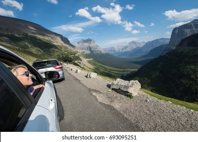 SEPT 1 2016 - WEST GLACIER, MONTANA: A female gazes out the car window, admiring the mountain scenery on Going to the Sun Road in Glacier National Park