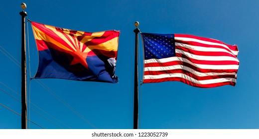 SEPT 13, 2018  Arizona, USA - Arizona and US Flag fly in a blue sky