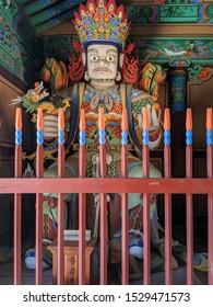 SEPT. 15, 2019-BUSAN, SOUTH KOREA ; Beomeosa Temple. Tourist pray at Wooden Korean Guardian Sculptures before entrance in Beomeosa Temple