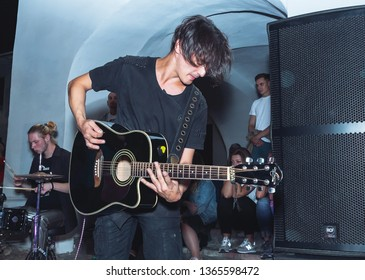 September 1, 2018 Minsk Belarus Street festivities in the evening city Man playing guitar in front of people on the street.