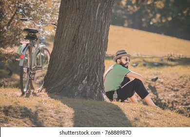 September 10, 2015, Petersburg, Russia, : Man dressed in hipster style arrived to park on bicycle and sits near tree for relaxing and drinking beer on nature, birds and sunny day on the background
