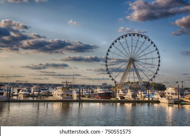 September 10, 2017, Oxen Hill, Maryland, USA: Boats docked on the national waterfront sit in front of the pier and ferris wheel in late summer.