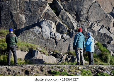 "September 12, 2018, Qaqortoq, Greenland.  Visitors In Qaqortog, Greenland View Stone Carvings From The 1990's Which Were Part Of An Art Project Known As ""Stones And Man""."