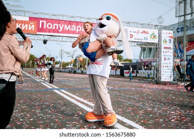 September 15, 2018 Minsk Belarus Half Marathon Minsk 2019 Woman with a microphone comments on how a man in a hare suit raised an athlete woman