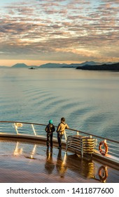 September 17, 2018 - Clarence Strait, AK: Warmly dressed couple, early morning on Lido Deck of The Volendam cruise ship.