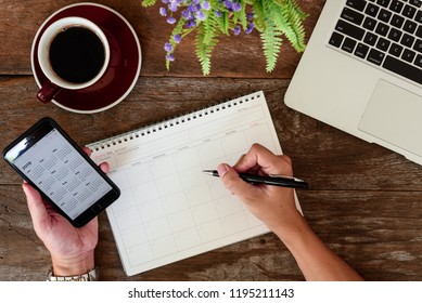 SEPTEMBER 17, 2018: Working table top with organizer for monthly planing with hands of man hold Iphone 8 plus use calendar application with year 2019