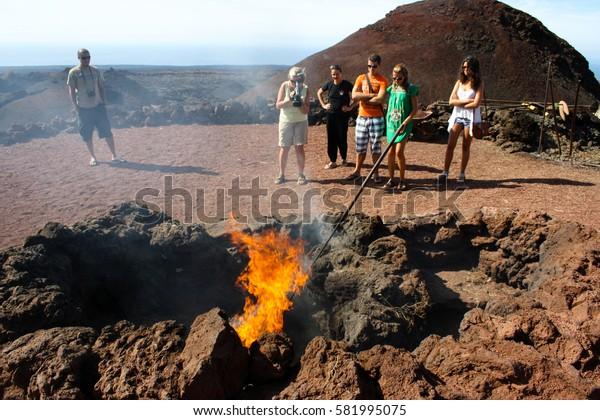 September 17th, 2012, Timanfaya National Park, Las Palmas, Lanzarote, Spain - park employee displays the high temperatures of the soil