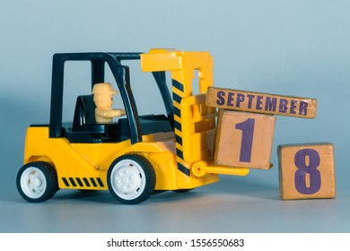 september 18th. Day 18 of month,  Construction or warehouse calendar. Yellow toy forklift load wood cubes with date. Work planning and time management. autumn month, day of the year concept.