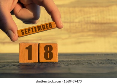 september 18th. Day 18 of month, calendar on a wooden cube. a woman's hand puts the name of the month on the number of the month on a wooden background autumn, day of the year concept.