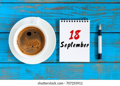 September 18th. Day 18 of month, morning cappuccino cup with loose-leaf calendar on analyst workplace background. Autumn time. Empty space for text