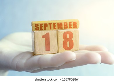 september 18th. Day 18 of month,Handmade wood cube with date month and day on female palm autumn month, day of the year concept