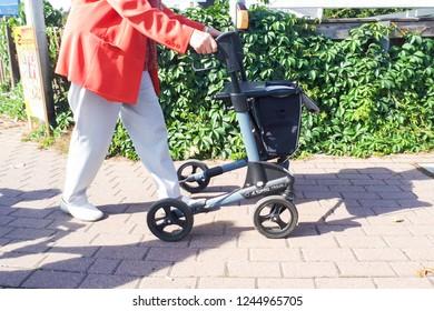 September 2, 2018 - Flohmarkt, Germany: An elderly woman is walking while holding a walker
