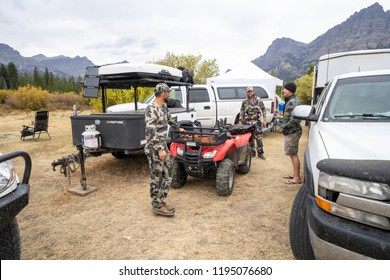 SEPTEMBER 20 2018 - DUBOIS, WY: Adult male hunters gather around base camp, discussing plans for the day. Trucks and 4x4 wheelers in the photo. Wearing camouflage
