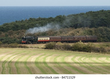 September 2011. Preserved ex British Railways  9F steam locomotive working a passenger train on the North Norfolk Railway between Sheringham and Holt. Set against   green trees and the blue North Sea.