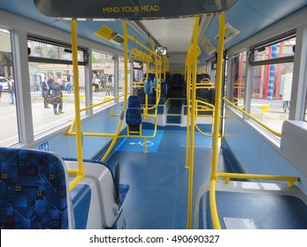 September 2016, The inside of an empty single-decker, all electric London bus - the shot looks down from the middle of the bus to the rear entrance. The reserved wheelchair space is visible.