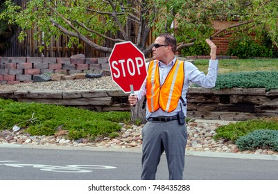September 2017 Denver CO USA; a man directs traffic outside a grade school to help keep kids safe while crossing the street