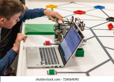 September, 2017. Minsk, Belarus. Teenager boy constructs and programmes Lego Robot Mindstorms EV3. Education of children and teenagers. Stem. Scratch. Competition. Laptop.