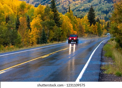 "SEPTEMBER, 2018 - OURAY, SILVERTON COLORADO - red jeep drives Wet autumn road goes from Ouray to Silverton Colorado, the ""Million Dollar Highway"" with color, Route 550"