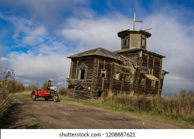 September, 2018 - Touglas. Red motorcycle on the background of the destroyed church. Russia, Arkhangelsk region, Vinogradovsky district, village Tulgas