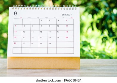 September 2021 Calendar desk for organizer to plan and reminder on wooden table on nature background.