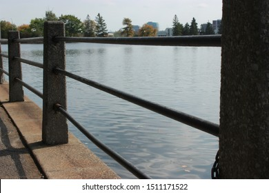 September 21, 2019 - Ottawa, Canada - A guard rail along the Rideau Canal bike path near Dow's lake with trees in the background
