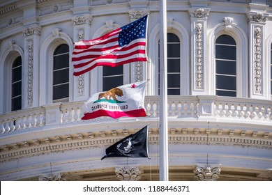 September 22, 2018 Sacaramento / CA / USA - The US flag, the California flag and the POW-MIA flag waving in the wind in front of the Capitol State Building in downtown Sacramento
