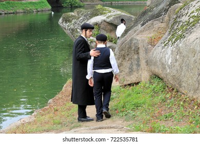 September 23, 2017. 2 boy, a family of Hasidic Jews,  in traditional clothes walk in the park in Uman, Ukraine, Jewish New Year, Rosh-ha-Shana. The older brother takes care of the younger one
