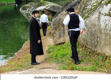 September 23, 2017. 3 boys, a family of Hasidic Jews, in black traditional clothes walk in the park in Uman, Ukraine, the time of the Jewish New Year, Rosh-ha-Shana