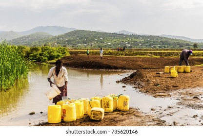 September 23, 2017 Near Kagoro, Nyanza Provience, Kenya. African woman filling yellow water containers with stream water for a building site. Man in background preparing to transport. Rural scene.