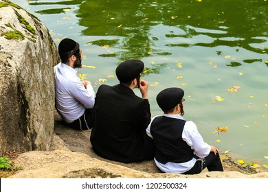 September 23, 2017. Uman,Ukraine.  A family of Hasidic Jews, 3 boys, in traditional black clothes  sitting in the autumn park, the time of the Jewish New Year.