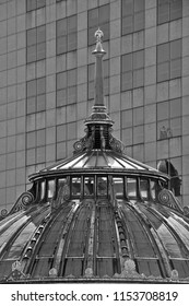 September 23, 2017: A vertical black and white image of the juxtaposition of old and modern architecture on two buildings on an urban downtown street.