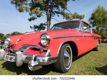 September 24, 2017; Mimizan Plage France: red Studebaker in sunshine at a green meadow, side view, american classic car parked in blue sky.