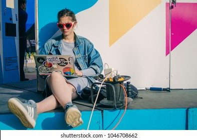 September 24, 2017. Rostov-on-Don. Russia. Girl dressed in a youth style sits near the graffiti and looks at the laptop at a festival of street art in Rostov-on-Don