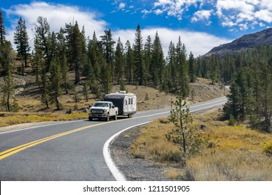 September 29, 2018 Dardanelle / CA / USA - Truck towing a camper on the highway through the Sonora Pass on a sunny day, Sierra mountains