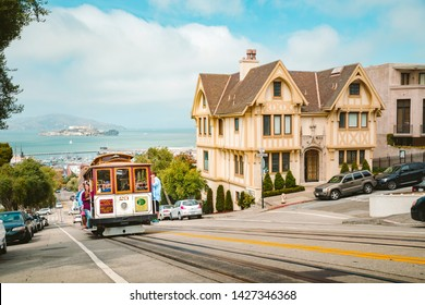 SEPTEMBER 3, 2016 - SAN FRANCISCO: Powell-Hyde cable car climbing up steep hill in central San Francisco with famous Alcatraz Island in the background on a sunny day with blue sky, USA.