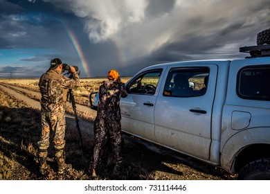September 30 2017 - DUBOIS, WYOMING: Two hunters use cameras and spotting scope to check out a rainbow after a storm.