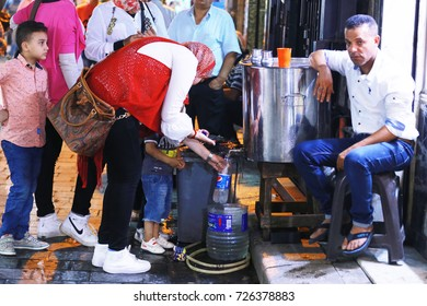 September 30, 2017-Cairo, Egypt: A woman taking drinking water at a night market in Cairo, Egypt
