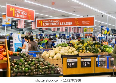 September 4, 2018 San Jose / CA / USA - People shopping in the food and vegetable area of one of Walmart's stores in south San Francisco bay area; Banners advertising the low price leader status