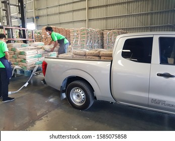 September 5, 2019 Ubon Ratchathani. Employees are carrying cement bags in the back of the pickup truck.